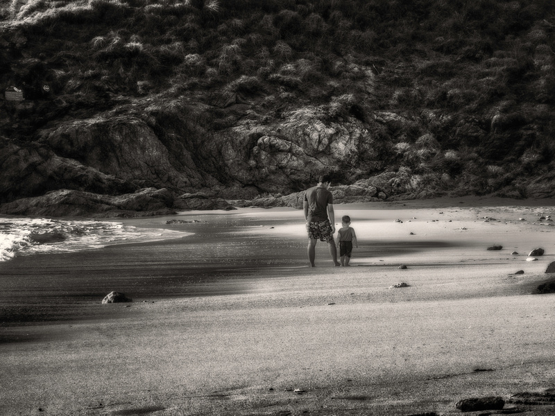 father son walking on the beach sunset B/W